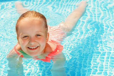 Encantadora niña nada en la piscina. El niño está sonriendo y mirando a la cámara.
