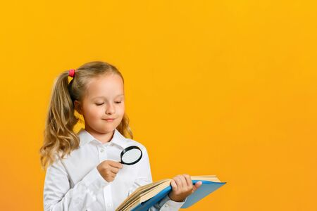 Little girl is reading a book on the table with a magnifying glass on a yellow background. The concept of education. Back to school.
