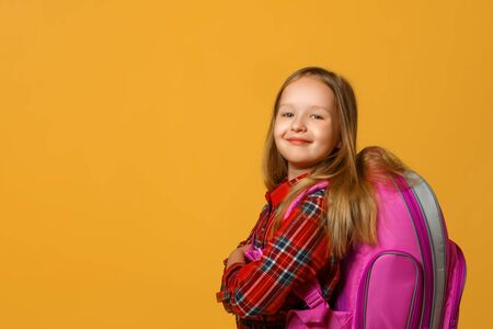 Portrait of a little girl schoolgirl on a yellow background. The child has a backpack behind his back. Back to school. The concept of education.