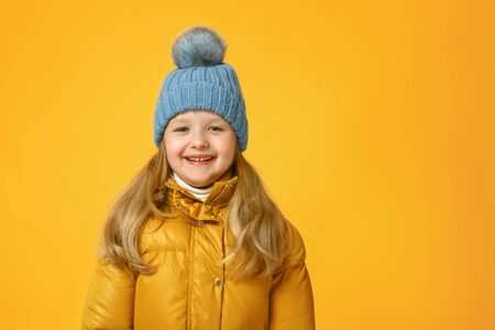 Portrait of a cheerful little girl in jacket and knitted hat over yellow background. Autumn concept.