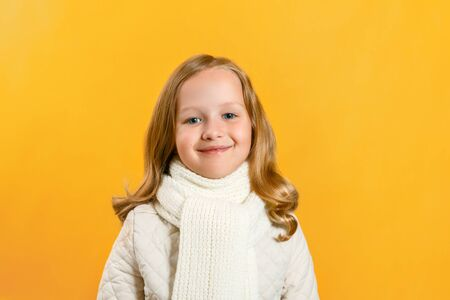 Portrait of a cute charming little girl in a jacket and scarf over a yellow background. Autumn concept. Copy space.