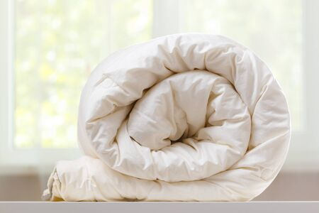 A folded rolls duvet is lying on the dresser against the background of a blurred window. Household. Imagens
