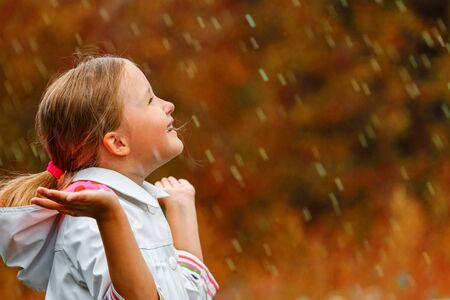 Side view of a cute charming little girl standing in the autumn park in the rain. The child reaches out and collects drops in the palm of his hand. Blurred background.