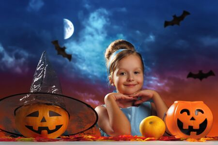 Halloween celebration. Charming little girl in a princess costume on the background of the evening moon sky. Imagens