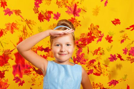 Little girl in a costume of Princess Cinderella with falling autumn leaves. The child put his palm to his forehead and looks at the camera. Concept for autumn, holiday, halloween, sale.