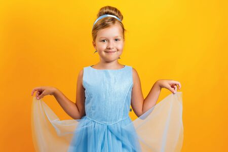 Charming little girl in a costume of Princess Cinderella on a yellow colored background. Concept for autumn, holiday, halloween.