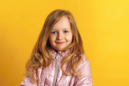Portrait of a cute little girl in a jacket on a yellow background. Autumn and winter concept.