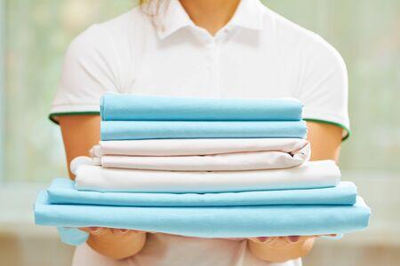 Gros plan de la main de la femme tenant une pile de draps pliés propres de couleurs bleu et blanc. Arrière-plan flou. Banque d'images