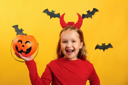 Halloween celebration. Little girl in a devil costume holds a bucket of pumpkin on a yellow background. Stock Photo