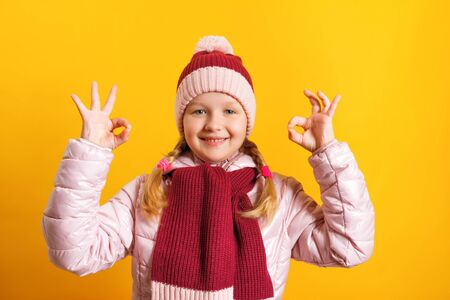 Little girl in a jacket, scarf and hat on a yellow background. The child shows an OK sign with two hands. The concept of autumn, success and education