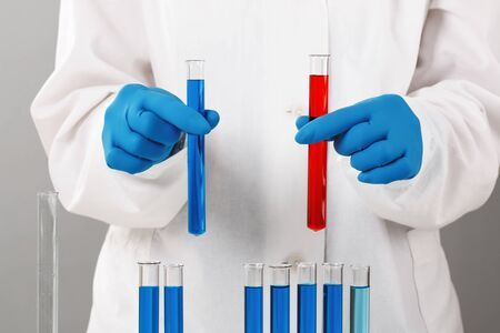In a chemistry lab, a pharmacist holds test tubes with red and blue liquids. Medical experiment. Chemist working on a test with blue gloves.