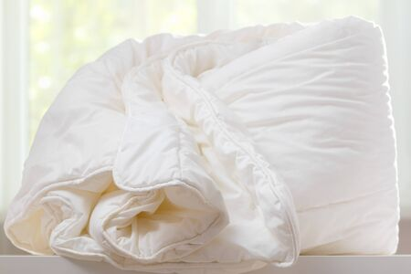 A duvet lies on a chest of drawers against a blurred window. Household.