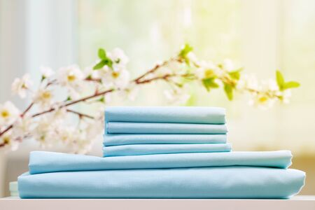 Blue colored bed sheets on the dresser. Blurred background. Flowering branch.