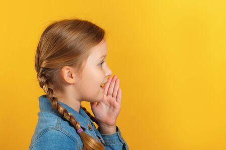 Vue latérale du profil enfant. La petite fille parle de côté, tient une main à une bouche.