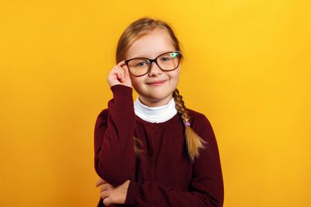 Clever little girl school girl corrects glasses. A child in a red sweater on a yellow background.