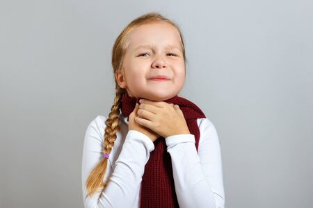 A little girl in a scarf suffers from a sore throat. The child holds on to the neck. The concept of the season of colds. Stock fotó