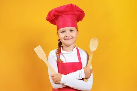 Beautiful little girl chef on a yellow background. The child holds in his hands a wooden spoon and spatula.