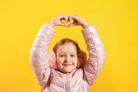 Cheerful little girl shows a heart with her fingers over her head. A child in a jacket and warm ear muffs on a yellow background. The concept of winter, christmas, new year.