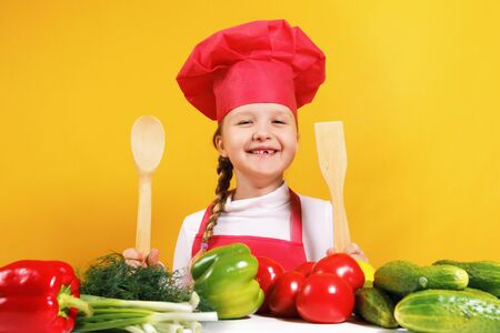 Beautiful little girl chef on a yellow background. The child sits at a table with vegetables and holds in his hands a wooden spoon and a spatula.