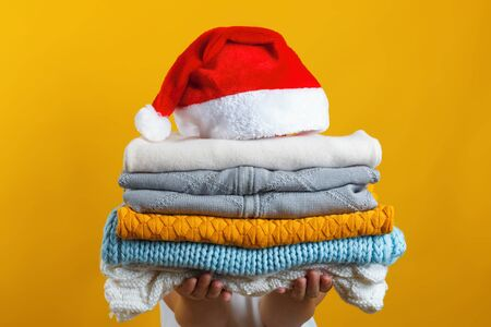 A woman holds a stack of warm knitted clothes, Santa hat is at the top. Winter and christmas concept.