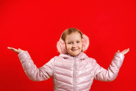 The little girl raised her hands up. A child in a jacket and warm ear muffs on a red background. The concept of happiness, winter.