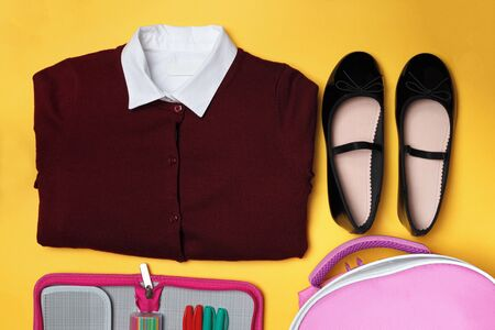 Top view of the composition of school clothes for children on a yellow background. Stockfoto