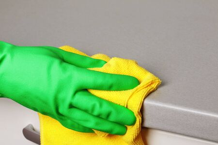 Closeup of a hand in a protective glove holding a napkin and wiping a countertop. Cleaning the kitchen.