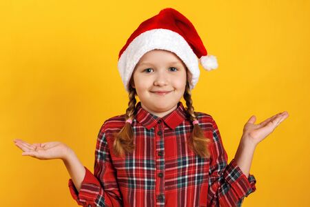Cute little girl in santa hat shrugs. Close-up of a child waiting for Christmas on a yellow background. Stok Fotoğraf