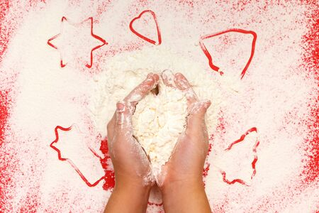 Children bake cookies for Christmas. Hands, star, tree, bell, heart, flour on a red background. Top view.