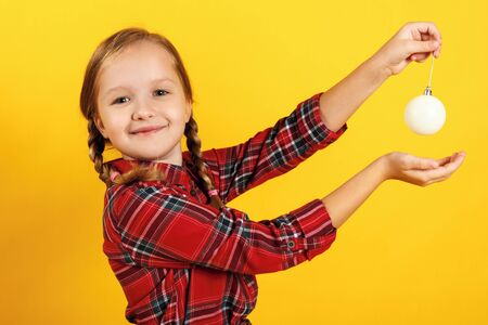Happy little girl with christmas ball toy. Close-up of a child in a red dress on a yellow background. Reklamní fotografie