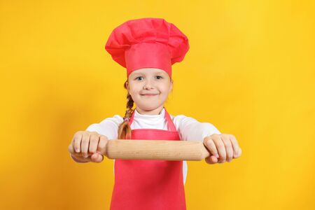 Beautiful little girl chef on a yellow background. The child holds in his hands a wooden rolling pin.