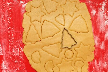 Christmas cookies. Raw dough star shape tree bell heart on a red board. Top view.