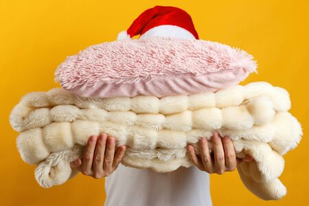 Woman in santa hat holding a stack of warm fluffy plaid and pillows on a background of a yellow wall. Imagens
