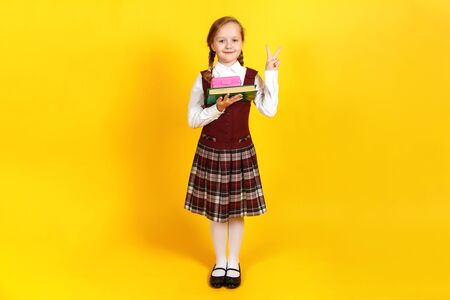 Portrait of a little girl schoolgirl on a yellow background. The child has a lunch box and a book in her hand, she shows a victory sign. Back to school. Education concept. Stock Photo