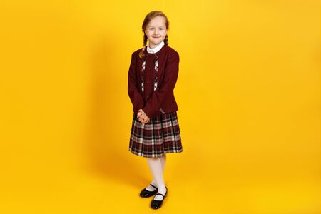 A full-length schoolgirl stands and looks at the camera. Cute little girl in uniform on a yellow background.