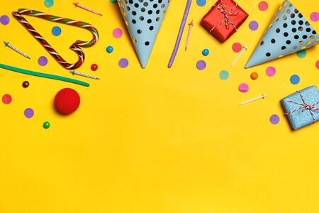 Birthday yellow background with party caps presents confetti candy. Copy space. Stock Photo