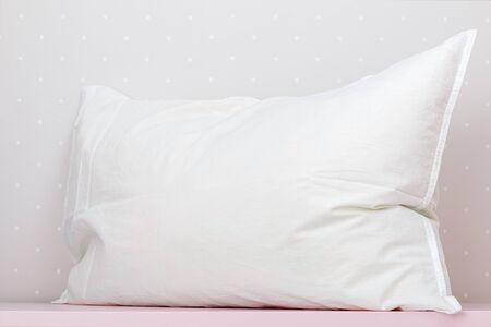 Zbliżenie białej poduszki na stole, na tle lekkiej ściany.