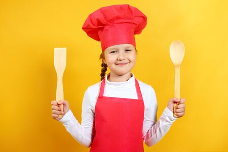 Beautiful chef child holds in his hands a wooden spoon and a spatula. Little girl in a cap and apron on a yellow background.