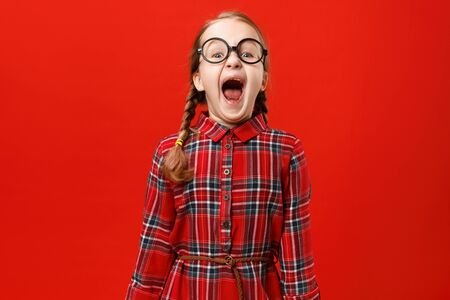Funny little girl in glasses shouts on a red background. Portrait of a child with open mouth.