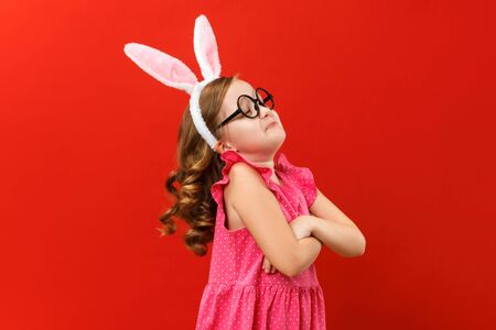 Happy easter. Cute little girl in bunny ears and glasses crossed her arms and looks away. Close-up baby on a colored red background.