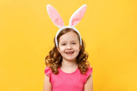 Happy cute little girl in easter bunny ears. Child close-up on a yellow background color.