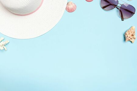 White summer hat, glasses, shells, corals on a blue background. The concept of vacation, sea, travel. Copy space.
