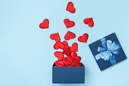Scattered red hearts from a blue open gift box on a colored background. The concept of love and Valentines Day. Zdjęcie Seryjne