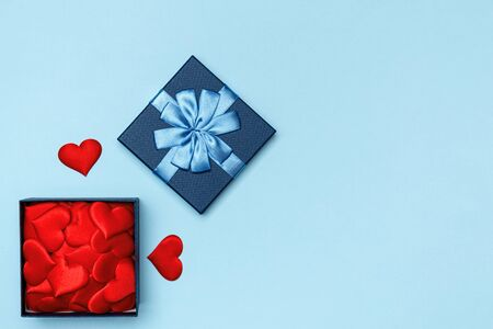 Blue open gift box with hearts on a colored background. The concept of love and Valentines Day.