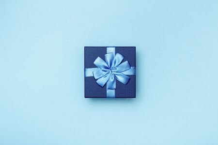 Blue gift box with bow on a colored background. Foto de archivo - 138471802