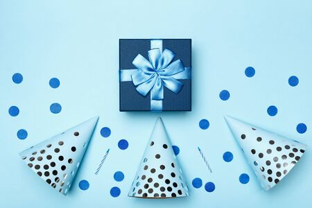 Birthday blue background composition with party gift present caps confetti candles top view flat lay.