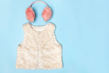 A set of warm clothes. Fluffy pink earmuffs and a white vest on a blue background. Top view flat lay copy space.