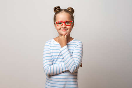 Portrait of a pensive thinking little schoolgirl girl in glasses on a white background. Child holding his chin with his hand.
