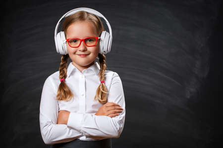 Close-up of a little girl cute student in headphones and glasses on the background of a school black board. Serious smart confident child has crossed arms and is looking at the camera.