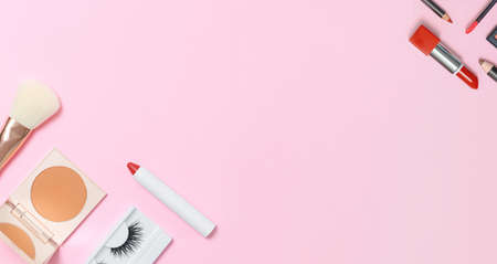 Decorative cosmetics on a pink background. Compact Powdery Makeup Brush False Eyelashes Lipstick Pencils. Banner copy space flat lay top view.